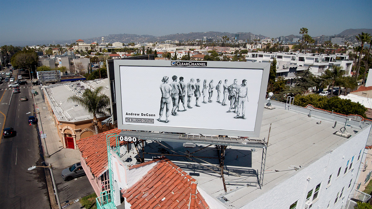 Aerial photo of a drawing on a billboard showing people standing in line, black and white, with Los Angeles city in the background