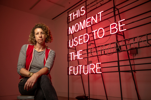 Alicia Eggert sitting on a stool that is next to a sign that says this moment used to be unimaginable.