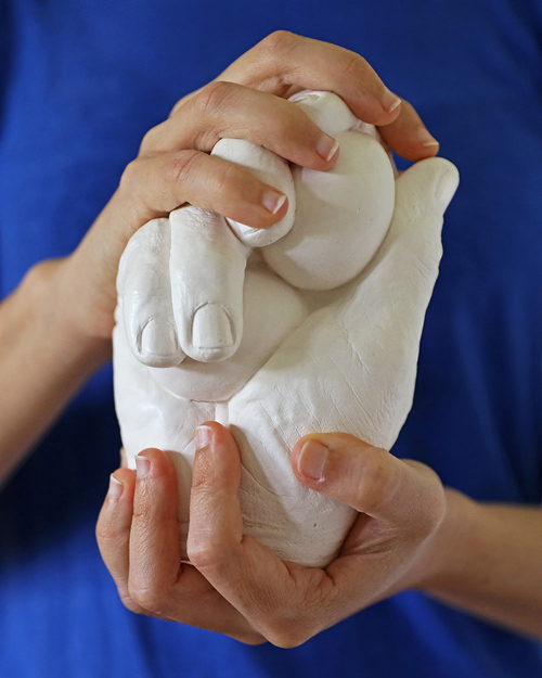 Human hands encircling plaster hands