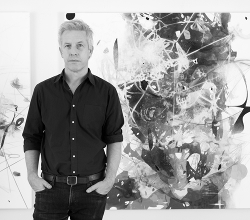 Artist Matthew Ritchie standing in front of an abstract painting, black-and-white photo
