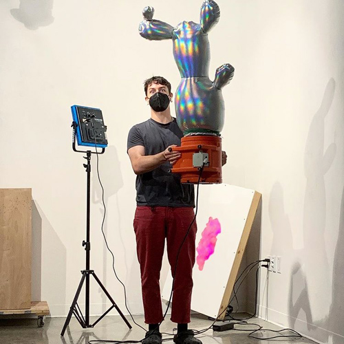 Sculpture student carrying a large mylar balloon shaped like a potted cactus
