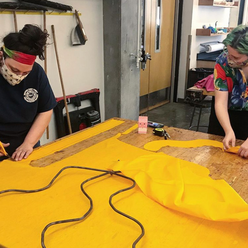 Two sculpture students working at a table cutting out large yellow shapes