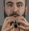 Pedram Baldari holding a woodwind instrument to his mouth