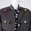 Detail of boxy black pinstripe jacket with randomly placed pockets and colorful dice buttons
