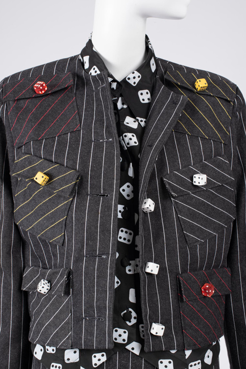 Detail of boxy black pinstripe jacket with randomly placed pockets and colorful dice buttons and blouse with black and white dice motif on mannequin.