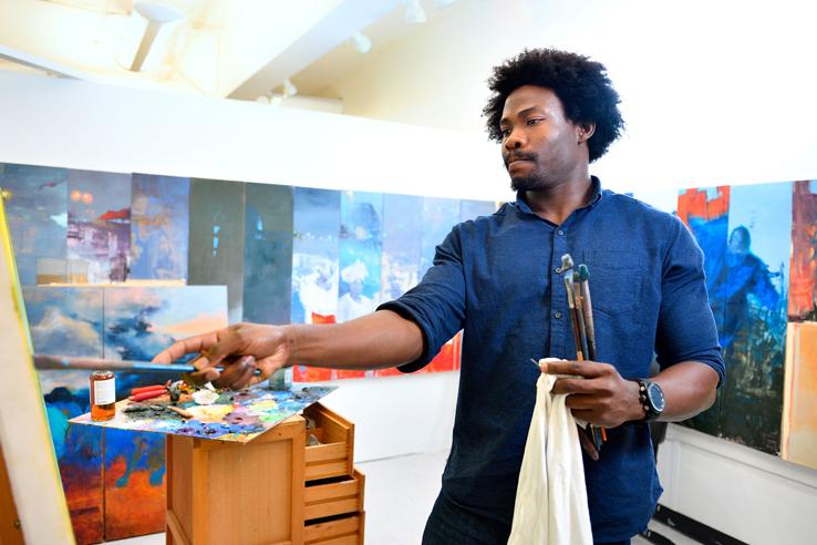 Augustine Uzor painting in his studio