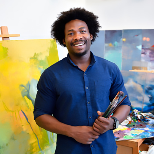 Augustine Uzor standing in front of a painting holding his art brushes